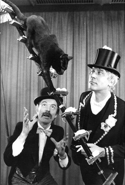 The fearlessness of these mice is not that they must sit on a narrow elevated ladder.  Nor that they must remain still as a black cat walks over them.  Their true bravery is they must perform in a show with two men dressed like this.